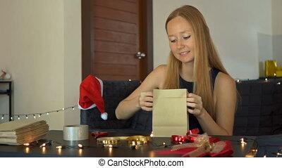рождество, женщина, ее, золото, year., ремесло, или, приход, молодой, presents., упаковка, бумага, настоящее время, красный, завернутый, новый, календарь, марки, children, лента