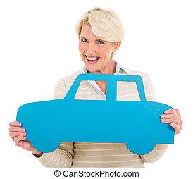 средний, aged, женщина, держа, автомобиль, символ