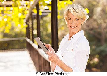 средний, aged, женщина, держа, таблетка, компьютер