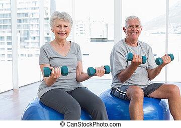 счастливый, старшая, пара, сидящий, на, фитнес, мячи, with, dumbbells