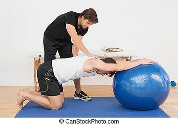 физическая, терапевт, assisting, молодой, человек, with, йога, мяч