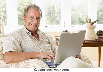 человек, в, гостиная, with, портативный компьютер, улыбается