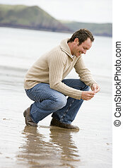 человек, crouching, на, пляж, улыбается