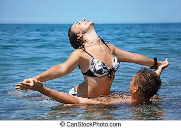 אישה יושבת, הצטרף, צעיר, חם, חוף, על, ים, ידיים, בעל, איש