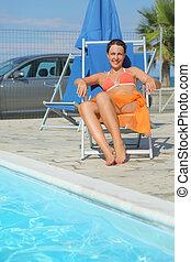 אישה צעירה, ב, תפוז, ביקיני, ו, פאראו, לשבת בחוף, כסא, ליד, צרף, ו, לחייך