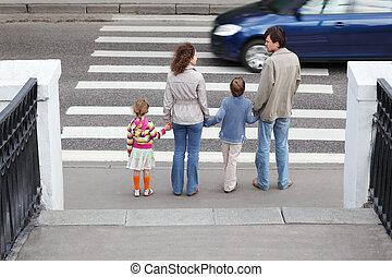 אמא ואבא, מחזיק, העבר, של, קטן, ילדה וילד, ו, לעמוד, ליד, הולך רגל עובר, אחרי, מכונית כחולה