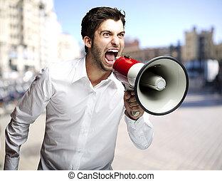 דמות, של, איש צעיר, לצעוק, עם, מגפון, ב, עיר