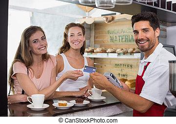 ידידים, עם, אישה מחזיקה, out, כרטיס אשראי, ב, בית קפה