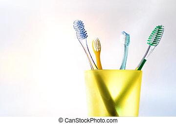 יומי, משפחה, של השיניים, לנקות, עם, צהוב, כוס של פלסטיק, עם, מברשות שיניים