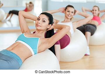 יפה, לאלף, כדורים, שלושה, צעיר מסתכל, שלהם, מצלמה, כושר גופני, abs., בגדים של ספורט, להתאמן, נשים
