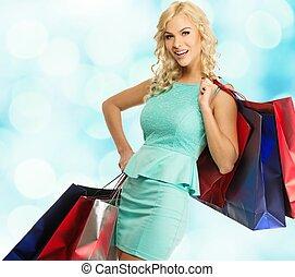 לחייך, צעיר, בלונדיני, אישה, עם, שקיות של קניות, מעל, רקע מטושטש