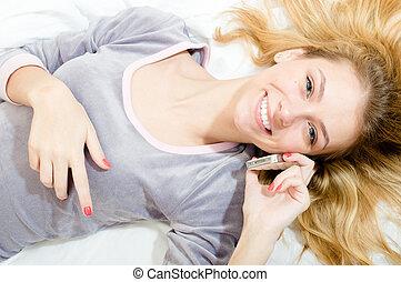 נאמן, יפה, לחייך, צעיר, בלונדיני, אישה, במיטה, ב, פיג'מה, לדבר, ב, ה, טלפון נייד, שמח מחייך, &, להסתכל במצלמה