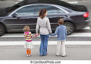 צעיר, אמא, מחזיק, העבר, של, שלו, קטן, ילדה וילד, ו, לעמוד, ליד, עובר דרך, אחרי, שחור, מכונית