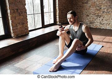 צעיר, לחייך, ספורטאי, להשתמש, טלפון נייד, בזמן, לשבת