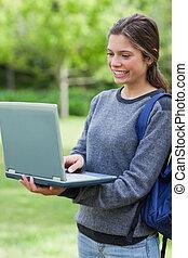 צעיר, סטודנט, להסתכל ב, ה, הקרן, של, שלה, מחשב נייד, בזמן, לחייך, ו, לעמוד, זקוף