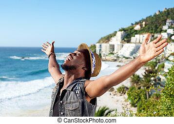 שמח, איש צעיר, עם, ידיים מתפשטות, פתוח, בחוף