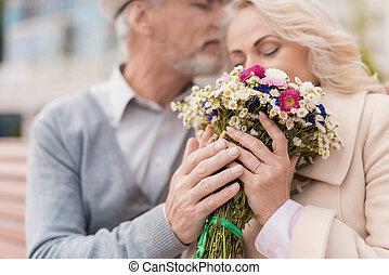 שני, גמלאים, are, לשבת, ב, a, ספסל, ב, ה, alley., ה, הזדקן, איש, gave, ה, אישה, flowers., הוא, מחזיק, שלה, העבר