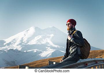 あごひげを生やしている, 観光客, 情報通, 人, 中に, サングラス, ∥で∥, a, バックパック, モデル, 上に, a, 路傍, こぶ, そして, 日没を見ること, に対して, ∥, 背景, の, a, 雪をいただいた山地
