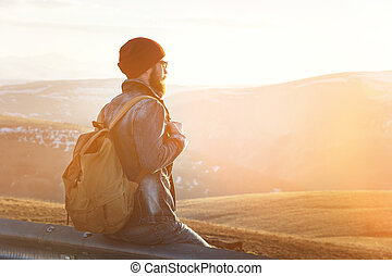 あごひげを生やしている, 観光客, 情報通, 人, 中に, a, 帽子, ∥で∥, a, バックパック, ある, 深く座る, 上に, a, 路傍, こぶ, そして, 日没を見ること, に対して, ∥, 背景, の, a, おおわれる 雪, 山