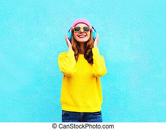 かなり, ファッション, 涼しい, 微笑の女の子, 音楽 を 聞くこと, 中に, ヘッドホン, 身に着けていること, a, カラフルである, ピンク, 帽子, 黄色, サングラス, そして, セーター, 上に, 青い背景