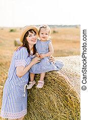 かわいい, 持つこと, 女の子, 彼女, mommy, の上, mother., 終わり, 干し草, 一緒に, フィールド, ポーズを取る, 魅了, 肖像画, 楽しみ, 赤ん坊, わずかしか, 歩くこと, 山, 娘, 日, モデル, 日当たりが良い, カメラ, 小麦, ベール, 若い