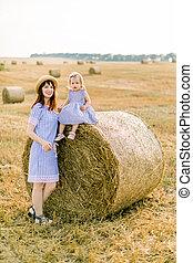かわいい, 持つこと, 女の子, 彼女, mommy, mother., しまのある, 干し草, 一緒に, フィールド, ポーズを取る, 魅了, 楽しみ, 赤ん坊, わずかしか, 歩くこと, 山, 娘, 日, モデル, 日当たりが良い, カメラ, 小麦, ベール, 服, 若い