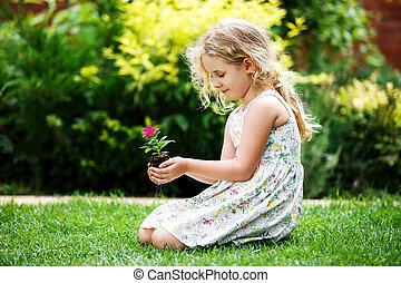 わずかしか, ブロンド, 女の子, 保有物, 若い, 花, 植物, 中に, 実地である, 緑, バックグラウンド。