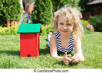 わずかしか, ブロンド, 女の子, 芝生の上に横たわる, ∥で∥, 家, おもちゃ