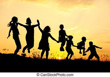 シルエット, グループ, の, 幸せ, 子供たちが遊ぶ, 上に, 牧草地, 日没, 夏