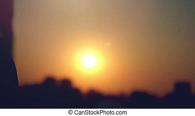 スローモーション, の, 2つの手, 拍手, 一緒に, によって, ∥, 太陽, 上に, シルエット, の, 都市, ∥において∥, 日没