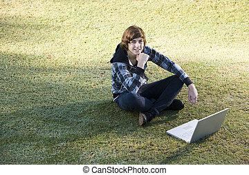ティーンエージャーの少年, ラップトップを使用して, 屋外で, 上に, 草