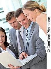 ビジネス チーム, 相談, プログラム, 上に, ラップトップ