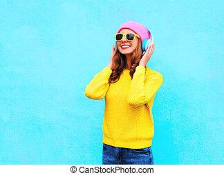 ファッション, かなり, 涼しい, 微笑の女の子, 音楽 を 聞くこと, 中に, ヘッドホン, 身に着けていること, カラフルである, ピンク, 帽子, 黄色, サングラス, そして, セーター, 上に, 青い背景