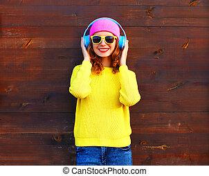 ファッション, かなり, 涼しい, 微笑の女の子, 音楽 を 聞くこと, 中に, ヘッドホン, 身に着けていること, a, カラフルである, ピンク, 帽子, 黄色, 編まれる, セーター, 上に, 木製である, 背景