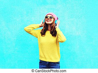 ファッション, 微笑の女の子, 音楽 を 聞くこと, 中に, ヘッドホン, 身に着けていること, a, カラフルである, ピンク, 帽子, 黄色, サングラス, そして, セーター, 上に, 青い背景