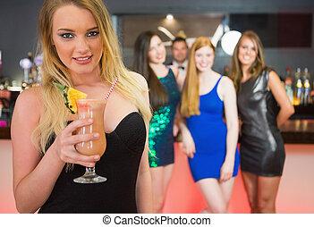 ブロンド, 魅力的, 女性の保有物, カクテル, 地位, の前, 彼女, 友人, そして, カメラを見る