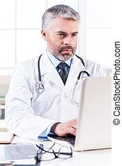 一般, practitioner., 成熟, 格瑞頭發, 醫生, 工作上, 膝上型, 當時, 坐, 在, 他的,...
