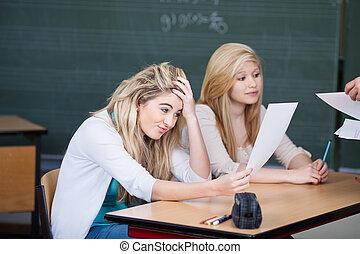 不滿意, 女生, 看, 問題, 紙, 當時, 教授, 給, 紙, 到, 同學, 在書桌