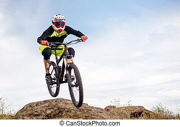 专业人员, 骑车者, 跳跃结束, 石头, 在上, the, 山地自行车, 在上, the, 岩石, hill., 极端体育运动, concept., 空间, 为, text.
