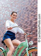 乗馬, 女, 角度, bike., 低い, 若い, 光景, 自転車, 微笑, 魅力的, 型, 彼女