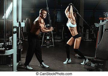 人, 同时,, a, 妇女, 训练, 肌肉, 在中, the, gym.