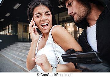 人, 泥棒, 脅すこと, ∥で∥, 銃, へ, おびえさせている, 叫ぶこと, 若い女性