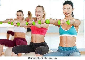 保持, 他們, 身体, 在, 形狀。, 三, 美麗, 年輕婦女, 在, 運動衣服, 藏品, dumbbells, 以及, 微笑, 在照像机, 當時, 坐, 上, the, 健身 球