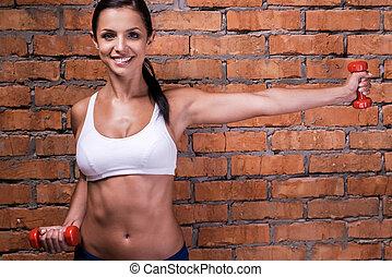 保持, 她, 身體, fit., 美麗, 年輕婦女, 在, 運動衣服, 行使, 由于, dumbbells, 以及, 微笑, 當時, 站立, 針對, 磚牆