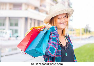 保有物, 買い物, 美しい, 間, 女の子, 袋, 見る, カメラ, 微笑, 下方に, 歩くこと, 通り