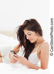 关闭, 妇女, 使用, 她, smartphone, 作为, 她, 躺, 在上, 她, 床