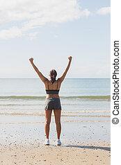 后部的見解, ......的, 微少, 年輕婦女, 提高, 她, 武器, 站在海灘上, 在, 明亮, 陽光