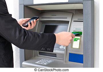 商人, 插入, a, 信用卡, 入, the, atm, 为了撤退, 钱, 同时,, 握住, a, 电话