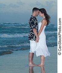 在海灘上扣留手的夫婦