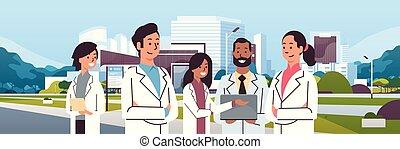 地位, 平ら, グループ, 背景, 医学, 上に, 現代建物, 一緒に, ユニフォーム, 混合, 医院, レース, 外面, 医者, 都市の景観, 肖像画, 横, チーム, 病院
